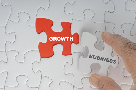 Hand holding piece of jigsaw puzzle with word BUSINESS GROWTH. Selective focus Standard-Bild - 116928370