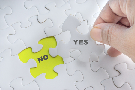 Hand holding piece of jigsaw puzzle with word YES NO. Selective focus Standard-Bild - 116928344