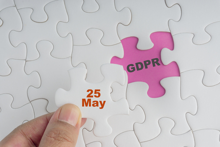 Hand holding piece of jigsaw puzzle with word GDPR. Selective focus Standard-Bild - 116928345