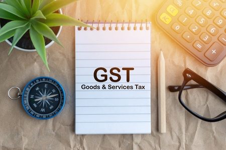 Notepad, flower vase, spectacle, pencil ,compass, calculator and words GST on wooden paper background. Business and education concept