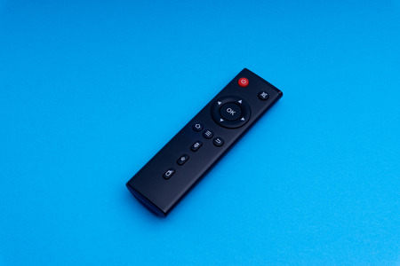 Remote control TV or radio isolated on blue background with selective focus and crop fragment