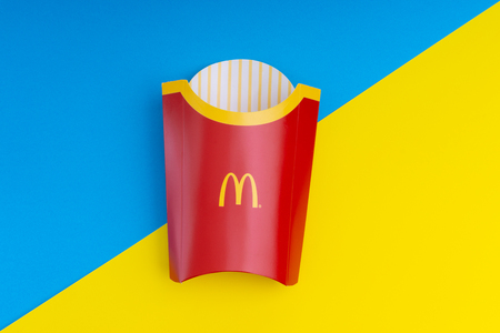 KUALA LUMPUR MALAYSIA - FEBRUARY 20, 2019: McDonald�s fries paper bags on blue and yellow background with selective focus