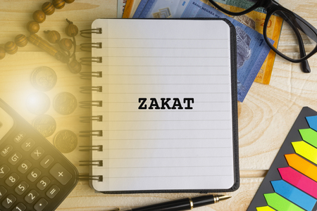 ZAKAT ( ISLAMIC TAX) inscription written on book with calculator, rosary, coins, banknotes, book, eyeglasses and pen on wooden background. Business, Insurance and Islamic concept Stock Photo