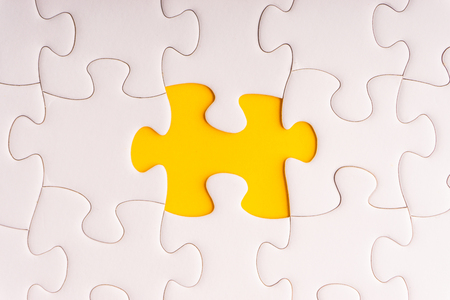 White jigsaw puzzle and missing pieces with selective focus and crop fragment Standard-Bild - 117925881