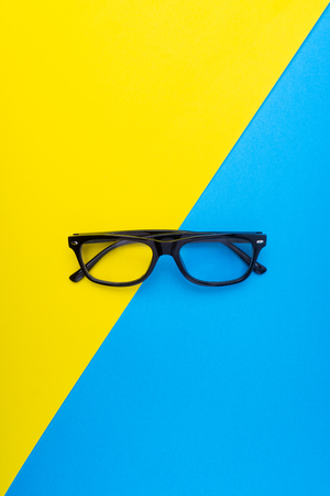 Black frame eyeglasses on blue and yellow background