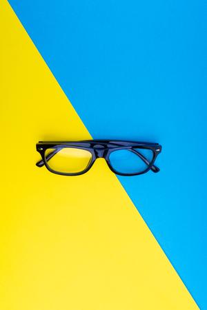 Black frame eyeglasses on blue and yellow background