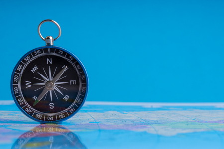 Compass on world map background. Selective focus