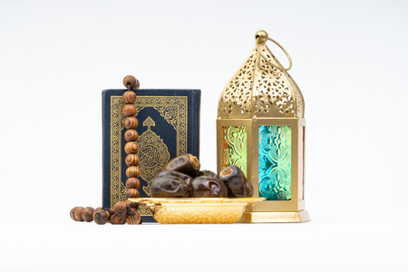 Lantern, Dates, Koran and Rosary on white background with selective focus and crop fragment. Ramadan, Religion and Copy space concept