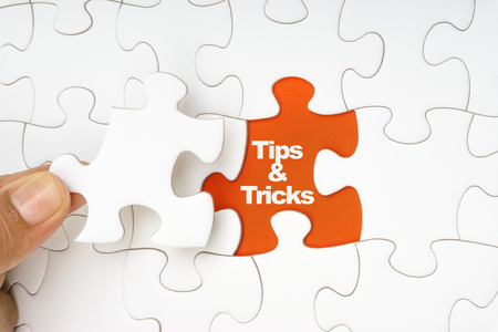 Hand holding piece of jigsaw puzzle with word TIPS & TRICKS. Selective focus Stock Photo