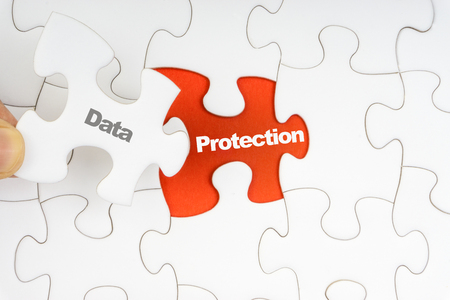 Hand holding piece of jigsaw puzzle with word DATA PROTECTION. Selective focus