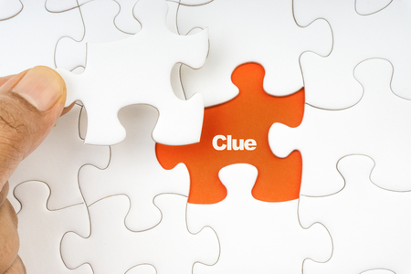 Hand holding piece of jigsaw puzzle with word CLUE. Selective focus Stock Photo