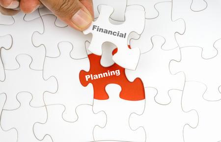 Hand holding piece of jigsaw puzzle with word FINANCIAL PLANNING. Selective focus Stock Photo