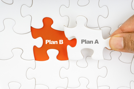 Hand holding piece of jigsaw puzzle with word PLAN A & PLAN B. Selective focus