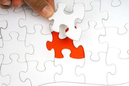 Hand put the last piece of jigsaw puzzle closeup to complete the mission. Selective focus and crop fragment Standard-Bild - 118978875