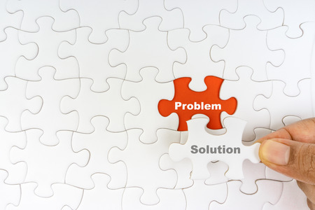 Hand holding piece of jigsaw puzzle with word PROBLEM SOLUTION. Selective focus Standard-Bild - 118978883