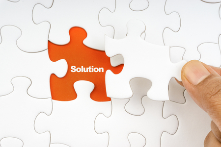 Hand holding piece of jigsaw puzzle with word SOLUTION. Selective focus