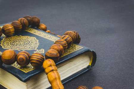 Holy Quran with tasbih or rosary beads over black background. Selective focus and crop fragment