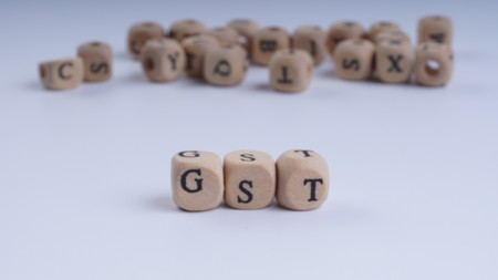 GST inscription on wooden alphabet over white background with selective focus