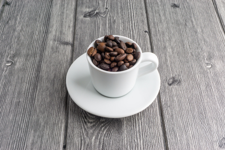 Coffee cup and coffee beans on wooden background. Top view and selective focus