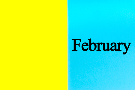 FEBRUARY written words on blue and yellow background. Calendar, Month, Date and Copy Space concept
