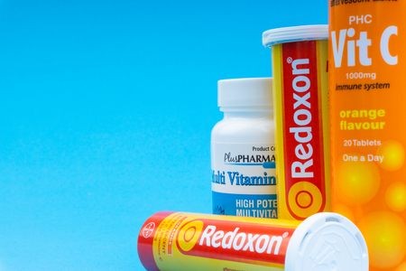 Multivitamin tablets and Vitamin C container closeup on blue background. Selective focus and crop fragment 報道画像