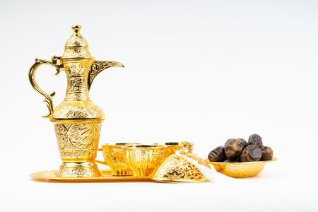 Premium dates and arabic coffee set on white background. Selective focus, copy space and Ramadan Kareem concept Banco de Imagens