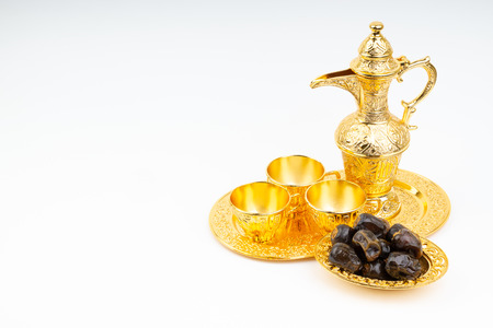 Premium dates and arabic coffee set on white background. Selective focus, copy space and Ramadan Kareem concept Imagens