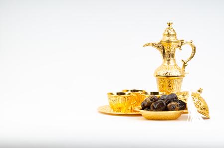 Ramadan kareem with premium dates, lantern and arabic coffee mug on white background. Selective focus, copy space and Ramadan Kareem concept Banco de Imagens
