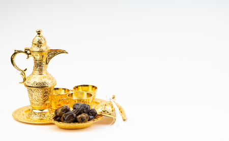 Premium dates and arabic coffee set on white background. Selective focus, copy space and Ramadan Kareem concept