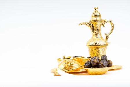 Ramadan kareem with premium dates, lantern and arabic coffee mug on white background. Selective focus, copy space and Ramadan Kareem concept