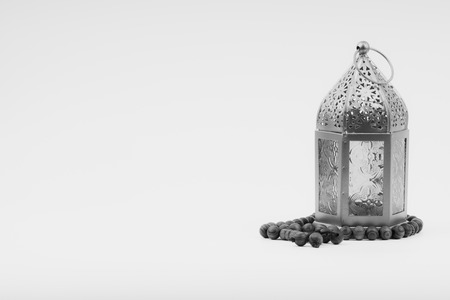 Lantern and rosary beads or tasbih on black and white. Selective focus, copy space and Ramadan Kareem concept