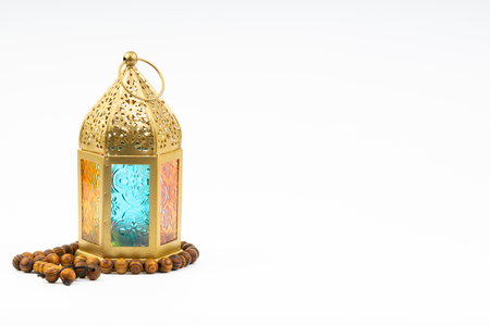 Lantern and rosary beads or tasbih on white background. Selective focus, copy space and Ramadan Kareem concept