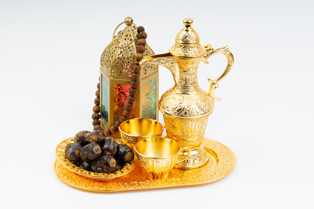 Premium dates, lantern and arabic coffee mug on white background. Selective focus, copy space and Ramadan Kareem concept