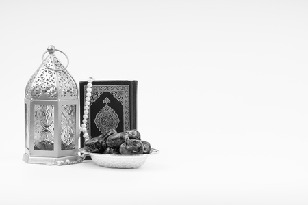Lantern, Dates, Koran and Rosary on white background with selective focus and crop fragment. Ramadan, Religion and Copy space concept. Black and White concept