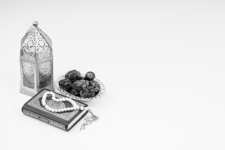 Lantaarn, dadels, koran en rozenkrans op witte achtergrond met selectieve aandacht en gewasfragment. Ramadan, religie en kopieer ruimteconcept. Zwart-wit concept