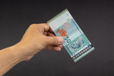 Hand holding Malaysia Ringgit MYR Currency Bank Notes. Selective focus