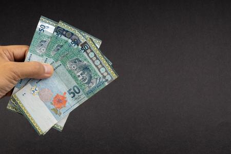 Main tenant la Malaisie Ringgit MYR billets de banque en monnaie. Mise au point sélective Banque d'images