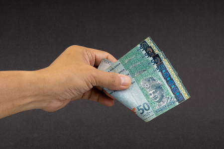 Hand holding Malaysia Ringgit MYR Currency Bank Notes. Selective focus Reklamní fotografie