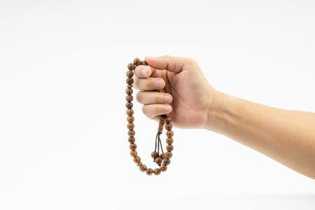 Hand holding a muslim rosary beads or Tasbih on white background. Copy space and selective focus Reklamní fotografie - 123738743