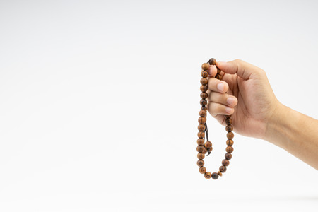Hand holding a muslim rosary beads or Tasbih on white background. Copy space and selective focus 스톡 콘텐츠