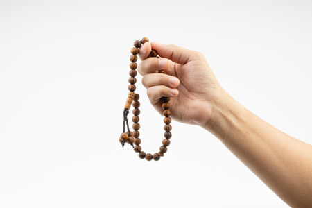 Hand holding a muslim rosary beads or Tasbih on white background. Copy space and selective focus Reklamní fotografie
