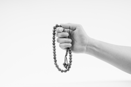Hand holding a muslim rosary beads or Tasbih on black and white. Copy space and selective focus Reklamní fotografie - 123738875