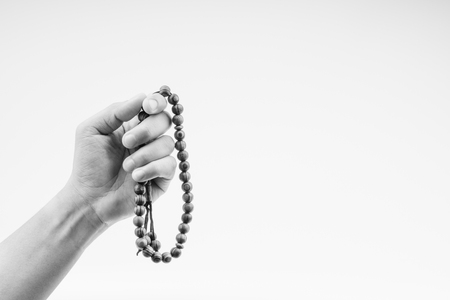 Hand holding a muslim rosary beads or Tasbih on black and white. Copy space and selective focus