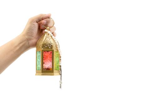 Hand holding arabic lantern isolate on white. Selective focus