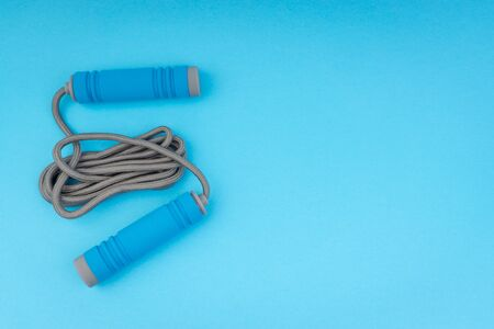 Skipping rope or jumping rope isolated on blue background. Selective focus and crop fragment