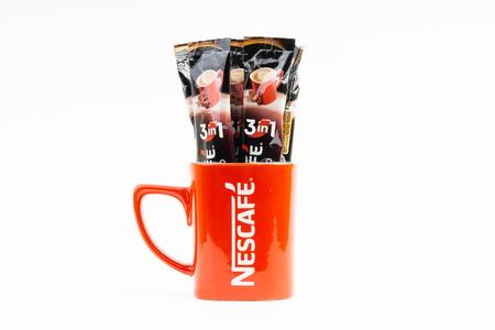 Kuala Lumpur, Malaysia - July 2, 2019: Sachet of instant Intenso Nescafe coffee with Nescafe mug on white background. Selective focus