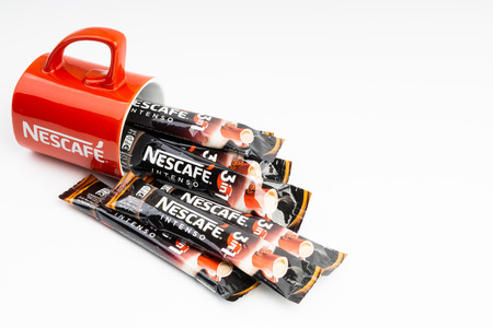 Kuala Lumpur, Malaysia - July 2, 2019: Sachet of instant Intenso Nescafe coffee with Nescafe mug on white background. Selective focus