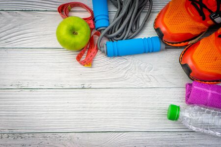 Top or flat lay view of towel, water, apple fruit, sport shoes and skipping rope with copy space area on wooden background. Healthy concept. Selective focus. Reklamní fotografie