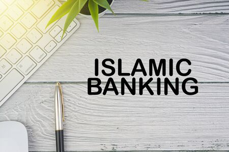 Flat lay, top view office table desk. Workspace with ISLAMIC BANKING inscription written with keyboard, mouse and pen on wooden background. Business, Insurance and Islamic concept Reklamní fotografie