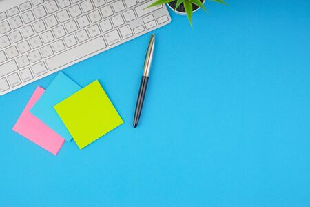 Flat lay, top view office table desk. Workspace with pen, sticky notes, decoration vase and keyboard on the blue background. Business Finance, Education and Copy Space concept